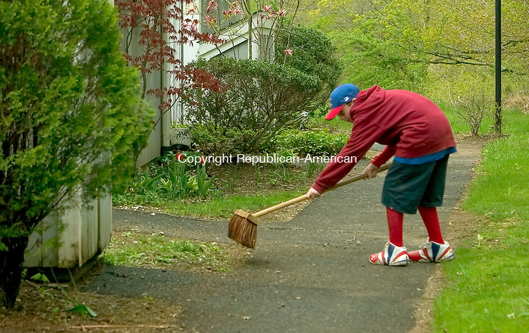 WOODBURY, CT- 04 MAY 2008 --050408JS04-Sam Rubinstein, 11, of Southbury, sweeps sidewalks for a resident of Spruce Bank Farm housing complex in Woodbury on Sunday. Sixth-grade students from the B'nai Israel religious school in Southbury were sprucing up the complex as part of Mitzvah Day, a day of good deeds. <br /> Jim Shannon / Republican-American