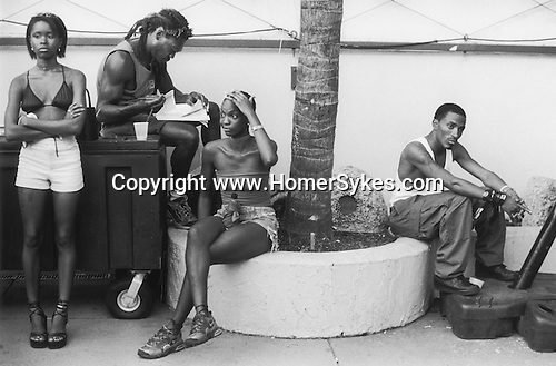 SOUTH BEACH, MIAMI FLORIDA  USA 1999.A GROUP OF YOUNG AFRICAN AMERICAN MEN AND WOMEN DRESSED IN SHORTS AND TEE SHIRTS SIT AND WAIT, ABSORBED ENTIRELY IN THEIR OWN THOUGHTS. ONE MAN DOES SOME BOOK WORK WHILE ANOTHER WOMAN HOLDS A WINE BOTTLE IN A PAPER BAG BETWEEN HER LEGS.