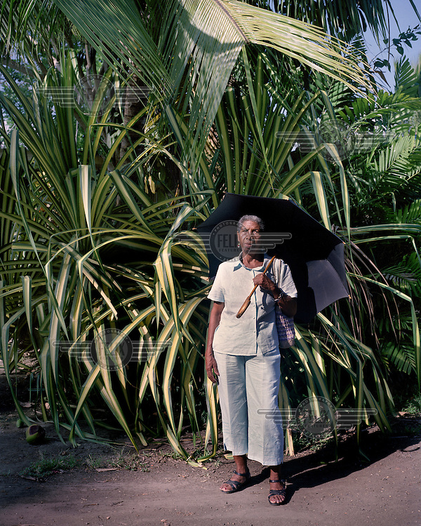 Albertina, a retired domestic worker at the Panama Canal Company Administrator's house, shelters from the sun beneath an umbrella in front of a huge palm. Pedro Miguel is a small town dating from the era when the French were attempting to build the canal.  <br /> <br /> The Panama Canal Zone is an area extending 8kms out, in each direction, from the waterway's central line, was a territory controlled by the United States between 1903 and 1979. After a 20 year period of joint administration, the Canal came under the full control of Panama in 1999. The Canal opened to shipping in 1914 and during its tenure was of great strategic importance to the US, enabling it to rapidly move its naval fleet between the Atlantic and Pacific Oceans. However, its economic value came not directly from shipping fees but from the stimulus to trade that the waterway created. One hundred years after it opened in 2014 it is due to have its locks upgraded to cater for the super sized container ships of the 21st Century.  <br /> During the era of American administration thousands of US citizens populated the Canal Zone, living and working under US law in towns built to American standards. Not all of these people returned north after the canal came under full Panamanian control many stayed on, their identities tied to the region.