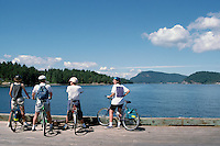 Four Cyclists admiring the View at Active Pass from Mayne Island, in the Southern Gulf Islands, British Columbia, Canada