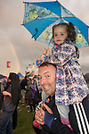 26-08-16 Electric Fields music festival, father with daughter on shoulder in rain with rainbow in backgroud at Drumlanrig Castle near Dumfries Scotland
