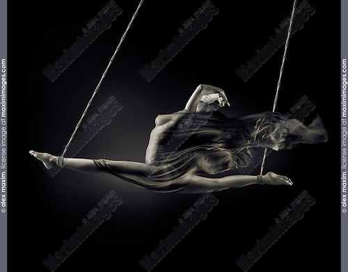 Surreal erotic photo of a beautiful nude woman swinging in a split suspended by her ankles with bondage ropes with flowing fabric wrapped around her bare body on black background. Black and white sepia toned.