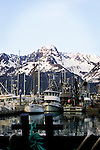 Fishing boats, Seward, Alaska, on reflective evening water, and the mountains behind.
