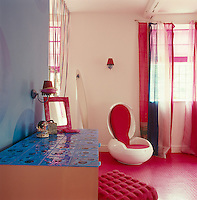 Bright colours in this child's bedroom are reflected in a red rubber floor, plastic Garden Egg chair by Peter Ghyczy and a blue-tiled chest of drawers