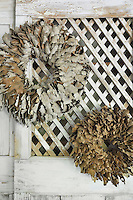 Two rustic wreaths are hung on a painted trellis.