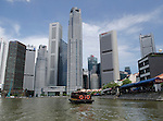 Bumboat in Singapore River with city skyline