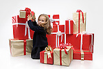 Little girl taking one present from a huge pile of Christmas gift boxes. Isolated on white background.