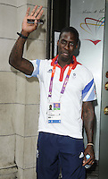 Dwain Chambers.The Prince Albert II of Monaco Olympians Reception, Old Burberry Building, Haymarket, London, England..August 9th, 2012.half length blue white t-shirt medal winner hand waving arm tattoos tongue .CAP/CAN.©Can Nguyen/Capital Pictures.