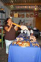 Griselda Gomez blowing into a pre-Hispanic trumpet in her handicrafts store in  the 19th century mining town of Mineral de Pozos, Guanajuato, Mexico.