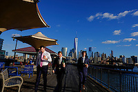 The World Trade Center and New York's lower Manhattan are seen at the background while people walk on a boardwalk during a sunny day in the Neighborhood of Exchange Place in New Jersey, 12/15/2015 Photo by VIEWpress