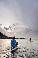 Stand up paddlers sit on their boards and rest while paddling on Lake Superior near Marquette Michigan.