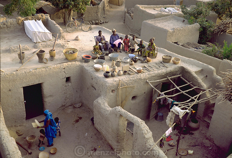 The Natomo family with all of their possessions on the roof of their home in Kouakourou, Mali. Published in Material World, page 14. According to tradition Soumana is allowed to take up to four wives; he has two. Wives Pama and Fatoumata are partners in the family and care for their many children together. They have separate households but share meals in the courtyard of Pama's house.  From Peter Menzel's Material World Project that showed 30 statistically average families in 30 countries with all of their possessions.