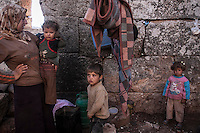 "In this Friday, Sep. 27, 2013 photo, shows a Syrian displaced family at the Kafr Ruma, an ancient roman ruins used as temporary shelter by those families who have fled from the heavy fighting and shelling in the Idlib province countryside of Syria. Dozens of families settled in the ancient ruins known as ""The Forgotten City"" and declared human heritage by UNESCO, when the clashes between opposition fighters and government forces broke out in the region since more than two years ago. (AP Photo)"