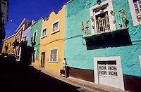 Mexican man walking with a suite case in a colorfull street in Guanajuato