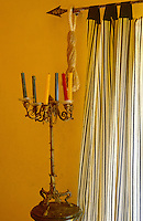 In a corner of the salon an ornate, antique candelabra is displayed against a buttercup yellow painted wall