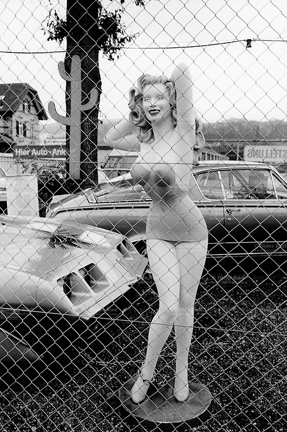 Switzerland. Zürich. A giant plastic pin-up dummy, wearing a mini skirt and a sexy top, stands in a yard of a sale shop for secondhand american cars. Car showroom.  © 1999 Didier Ruef