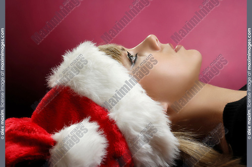 Young daydreaming woman in Christmas hat