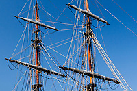 Rigging, ropes and cables each with a specific purpose, draws an intricate web among the masts and furled sails of the tall ship Lady Washington, moored at Jack London Square on the Oakland Estuary.
