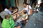Eileen Peralta and her 12-year old daughter Erin, who has autism, sit on the step of their home in the Malate neighborhood of Manila. They're being visited by other members of Kaisahan ng Magulang at Anak na Maykapansanan (Kaisaka), a mothers' group that carries out community based rehabilitation with families which have members with disabilities.