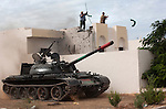 Anti-Gaddafi fighters remove a green flag from a rooftop while a tank rolls by in the Seven Hundred neighborhood of Sirte, Libya, Oct. 7, 2011. Revolutionaries pressed in to Col. Muammar Gaddafi's hometown, encountering fierce resistance snipers, rocket-propelled grenades, and mortars.
