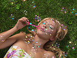 Young woman with soap bubbles having fun in the summer nature