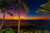 Palm trees pose on the shore as rays from the sunset pour through the clouds over the Caribbean waters. (Photo by Jeff Speer © www.JeffSpeer.com)
