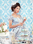 Beautiful asian woman in a luxurious blue dress standing with a cup of tea at a party table