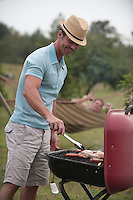Man enjoying grilling on a charcoal grill outdoors