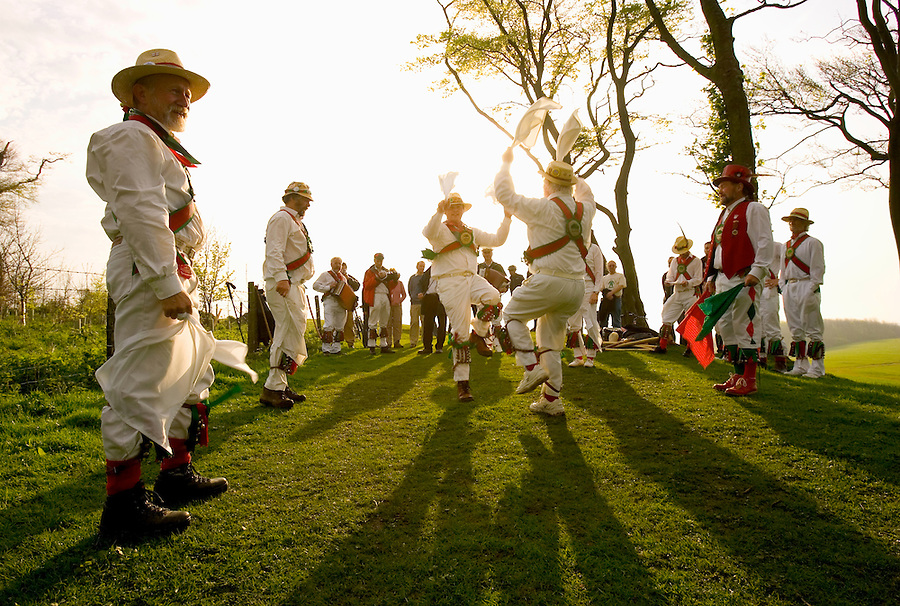 The Chanctonbury Ring morris dancers welcome the sunrise on May day - May 1st - atop the remains of the Iron Age hillfort of Chanctonbury Ring on the South Downs in Sussex UK