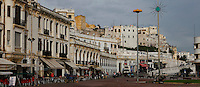 Seafront promenade, Tangier, Morocco, pictured on December 27, 2009. A long row of white houses, with awnings above the cafes at street level, stretches along the seafront. Old and new buildings are mixed together in the jumbled cityscape behind the promenade. Tangier, the 'White City', gateway to North Africa, a port on the Straits of Gibraltar where the Meditaerranean meets the Atlantic is an ancient city where many cultures, Phoenicians, Berbers, Portuguese and Spaniards have all left their mark. With its medina, palace and position overlooking two seas the city is now being developed as a tourist attraction and modern port. Picture by Manuel Cohen