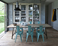 A scrubbed wood table is flanked by a set of six distressed metal bistro chairs in the kitchen/dining area