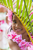 A girl wearing pink plumeria lei and haku head lei pose amid palm trees before a hula performance in Halei'wa, North Shore, O'ahu.
