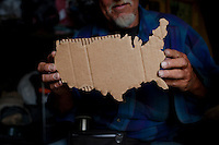 "Ventura, California, July 21, 2010 - A portrait of Gary Seymour holding a cardboard map of the United States in his camper. Mr. Seymour has been homeless off and on for the last thirty years. He currently lives in a camper parked left to him by his father that is parked in the driveway of a friend's mother. Because it is an illegal camp, Mr. Seymour is considered homeless. He says, ""I work odd jobs, landscaping and whatnot to make a little money. I am trying to get back on my feet."" Mr. Seymour is proud that he does not panhandle. ""I earn my own living without asking people for handouts."" ..."
