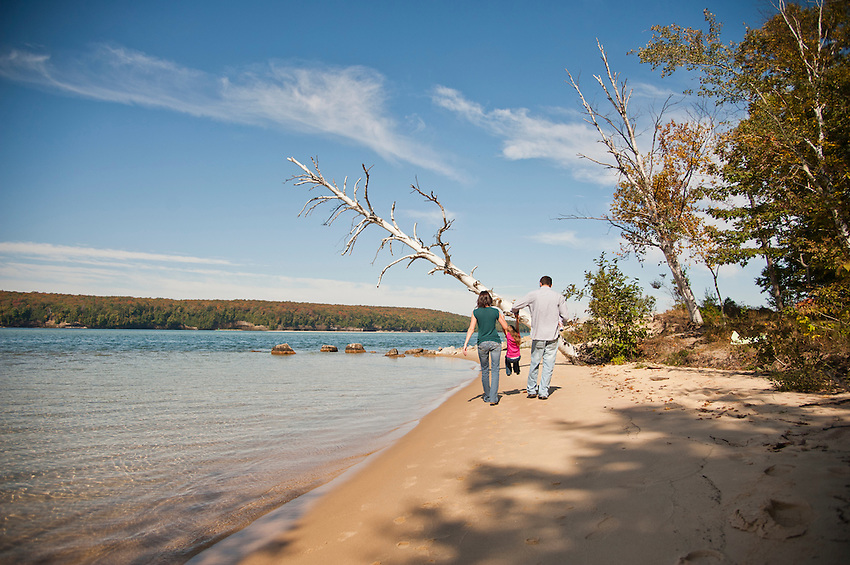 A young family enjoys a walk along the beach at Sand Point in Pictured Rocks National Lakeshore in Munising Michigan.