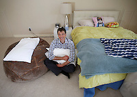 NWA Democrat-Gazette/DAVID GOTTSCHALK  Dan Sanker sits in his favorite personal space Thursday, September 15, 2016, the area that was between the two beds of his children where he would sleep to guarantee all a good night sleep for all at his family's home in Fayetteville.