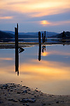 Idaho, North, Coeur d'Alene. Pilings in silhouette in the hazy, filtered, evening light reflect in the calm, shallow waters of Wolf Lodge Bay.