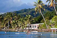 Tahitian woman paddling one-man canoe off palm lined shores of Raiatea