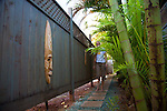 Paia Inn on the North Shore of Maui.  This hotel is located in a  quiet beachfront community and has a private entrance to Paia Bay.  The bamboo and fenced walkway that leads to Paia Bay from the hotel.