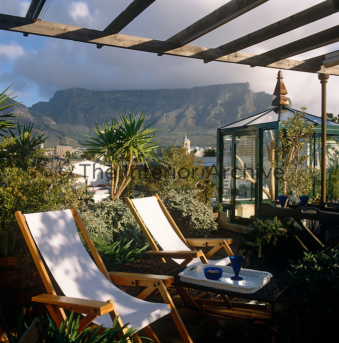 Two deck chairs arranged on the roof terrace of a house in Cape Town with views of Table Mountain in the distance