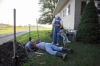 Caption 10<br /> John McCloud, left, and his son-in-law Mike Farmer, center, attempt to fix a leaking water line to Randell's house on September 25, 2013.