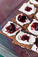 Strawberry jam and cream cheese on whole grain crackers.
