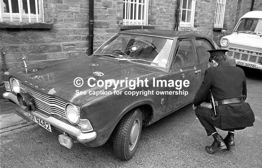 A  policeman at Victoria Police Station examines the car in which two RUC colleagues, Constable David Montgomery and Sergeant Peter Gilgun, were shot in a Provisional IRA submachine-gun attack in Londonderry, 27th January 1972. The two police were travelling along Creggan Road to their destination, Rosemount Police Station. They were the first policemen killed in Londonderry during the N Ireland Troubles. The bullet holes are circled. 197201270038c..Copyright Image from Larry Doherty c/o Victor Patterson, 54 Dorchester Park, Belfast, UK, BT9 6RJ..Tel: +44 28 9066 1296.Mob: +44 7802 353836.Voicemail +44 20 8816 7153.Skype: victorpattersonbelfast.Email: victorpatterson@me.com.Email: victorpatterson@ireland.com (back-up)..IMPORTANT: If you wish to use this image or any other of my images please go to www.victorpatterson.com and click on the Terms & Conditions. Then contact me by email or phone with the reference number(s) of the image(s) concerned.