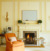A bright orange armchair stands beside a gas fire at one end of the formal drawing room