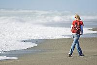 female tourist walking away from waves on isolated west coast beach near lake Mahinapua, New Zealand