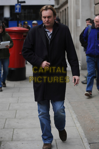 PHILIP GLENISTER .seen outside BBC Radio 2 Building, London, England, UK, April 1st 2010..two Phillip full length black coat jeans walking navy blue brown shoes .CAP/IA.©Ian Allis/Capital Pictures