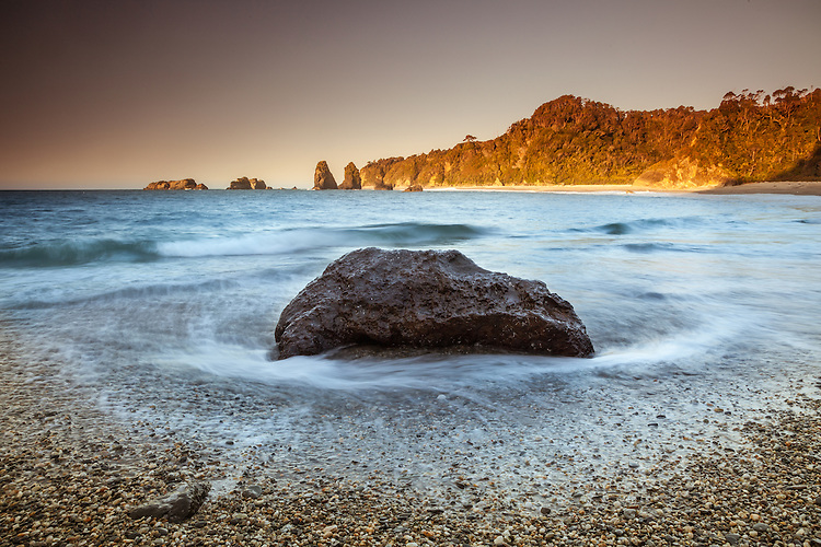 Waves surround a rock at Murphy's Beach, late afternoon. South Westland, New Zealand - stock photo, canvas, fine art print