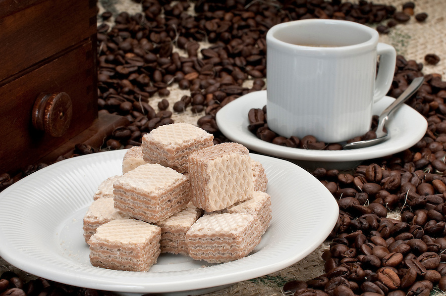Coffee beans and wafer cookies with cup and grinder.
