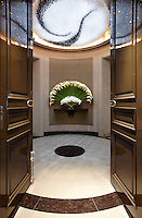 A view through a pair of double doors leading from one lobby to another. The hallway areas have curving walls and marble flooring.