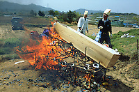 Korea. South Korea. Gimje area. Wonpyong. Funeral ceremony for an old man who died a few days ago. Traditional korean burial and burial service. Men burn the coffin which will be reduced to a blazing mass. The old man has been buried in a  shroud.  © 2002 Didier Ruef .