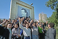 Boys and you men pose and sing in front of a picture of Saddam Hussein. The group was given basic military training along the banks of the Tigris river when, upon seeing the photographer, they started chanting and singing to praise Saddam Hussein.